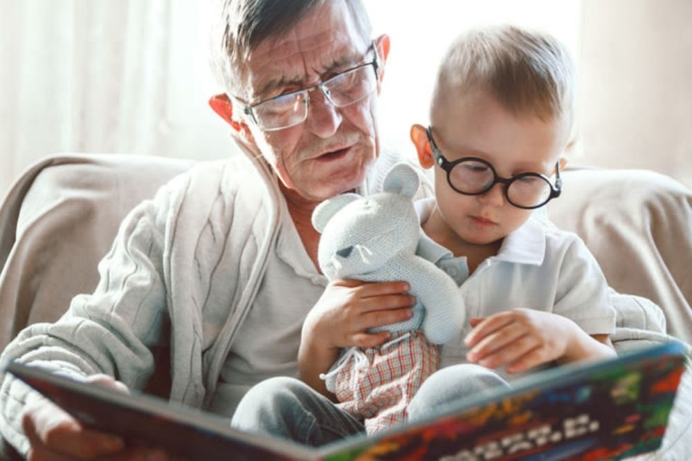 father and child reading with eyeglasses