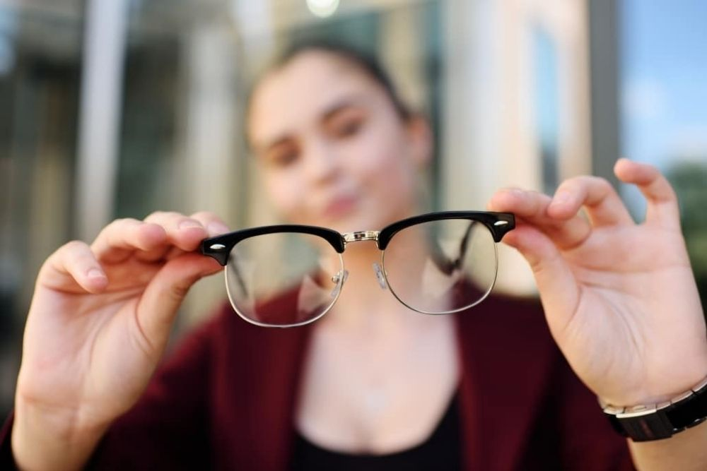 woman holding a pair of eyeglasses