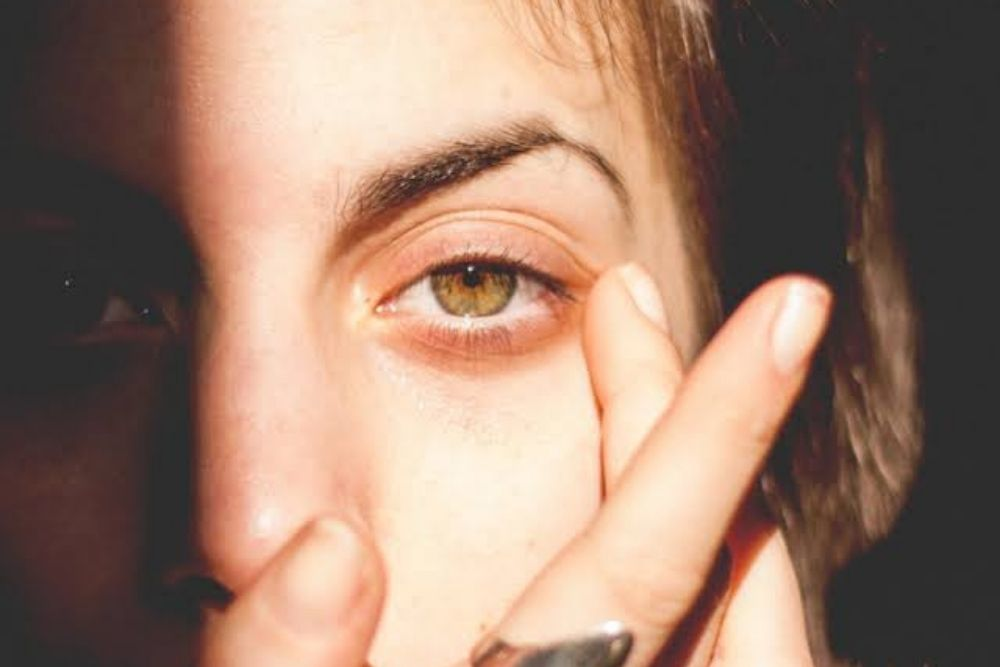 woman lightly touching one eye