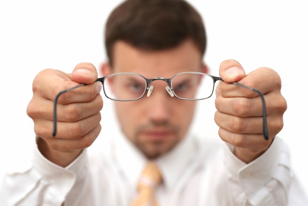 man holding eyeglasses with two hands