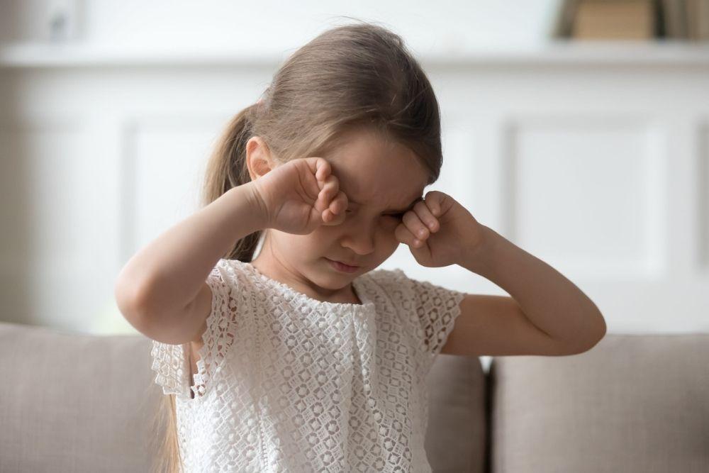 little girl rubbing her eyes