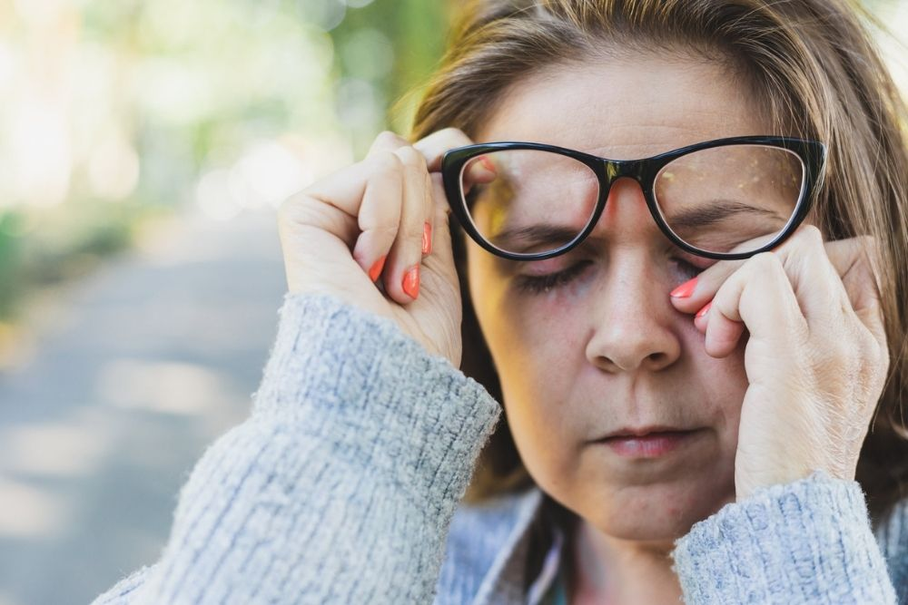 middle aged woman rubbing tired eyes