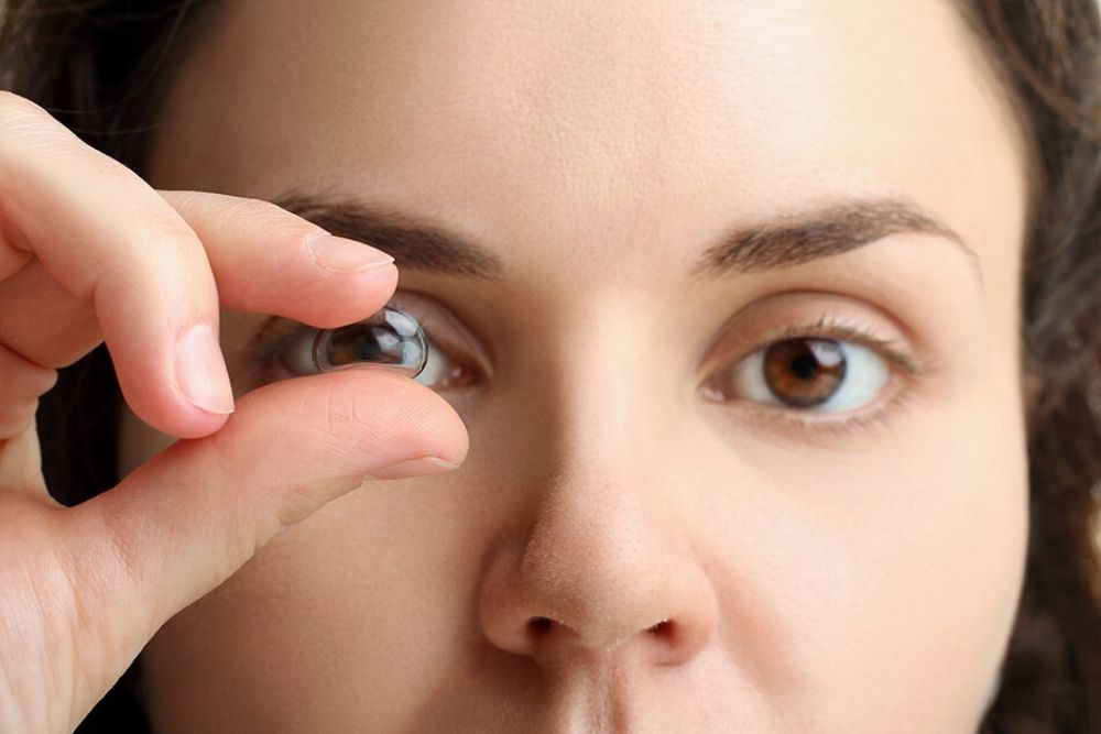 woman about to wear a piece of contact lens
