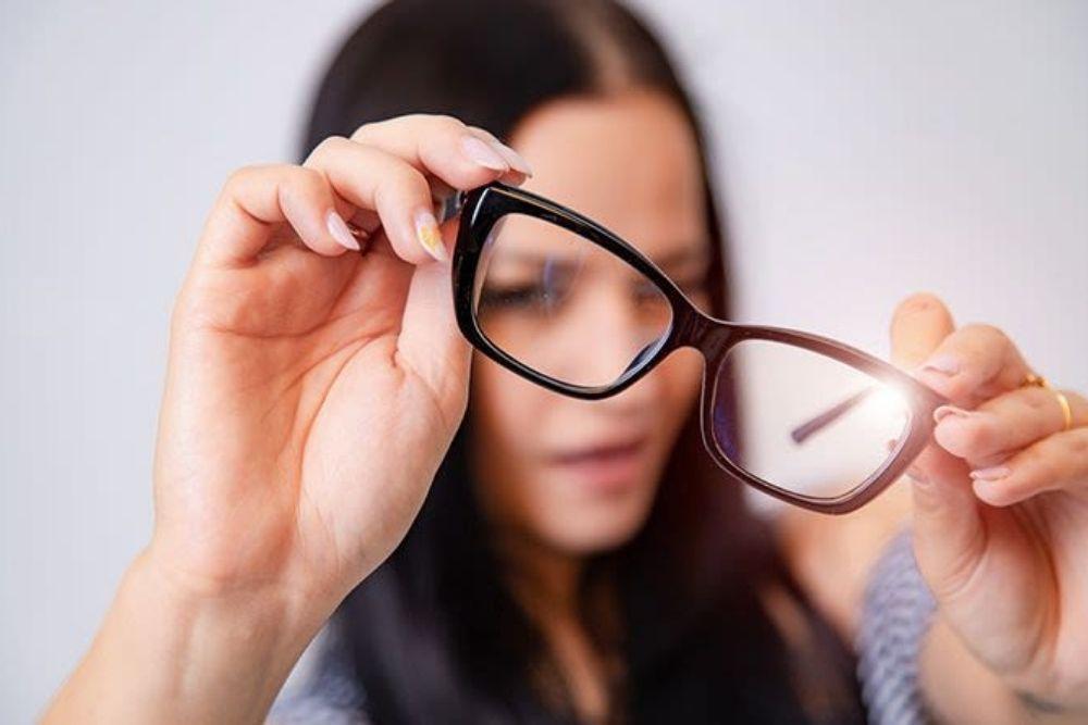 woman with narrowed eye looking at a pair of eyeglasses