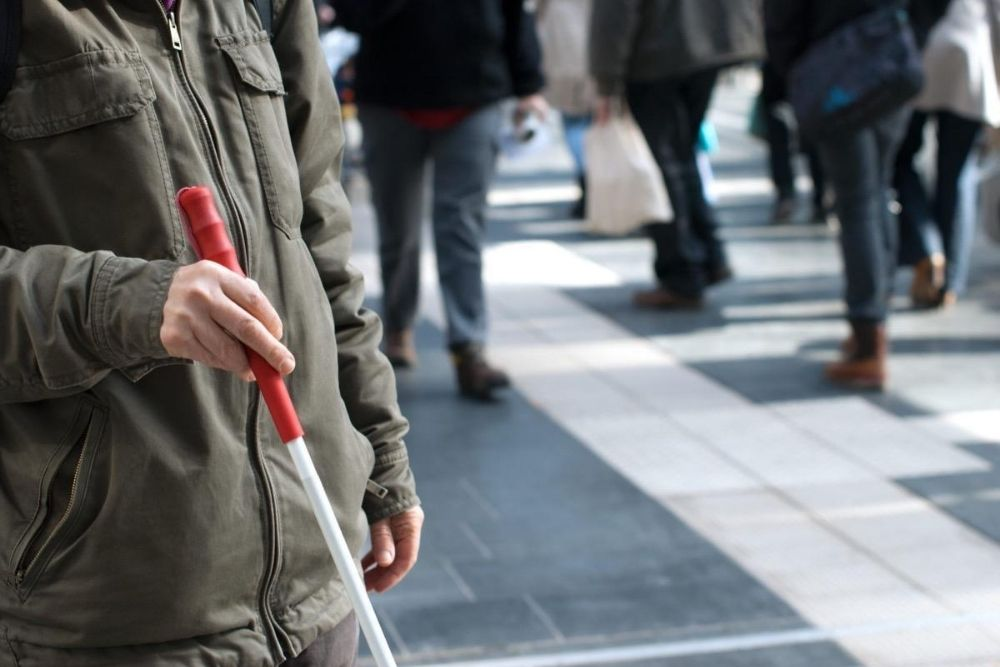 a person holding a white cane in public