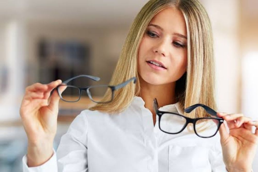 woman holding two pieces of eyeglasses