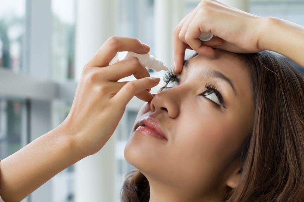 woman putting on eye drops