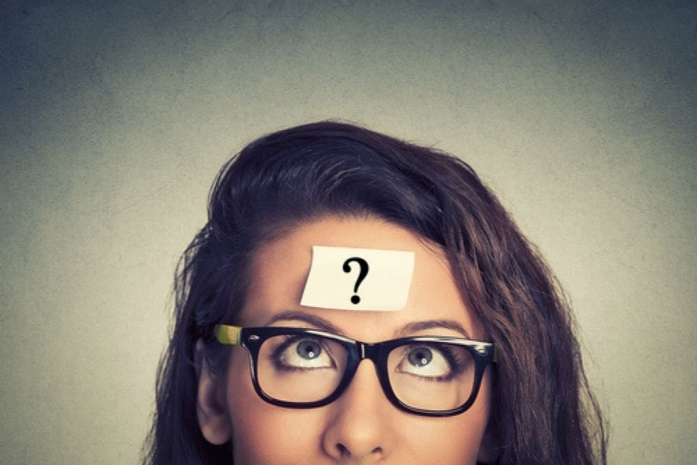 question mark on paper on woman's forehead