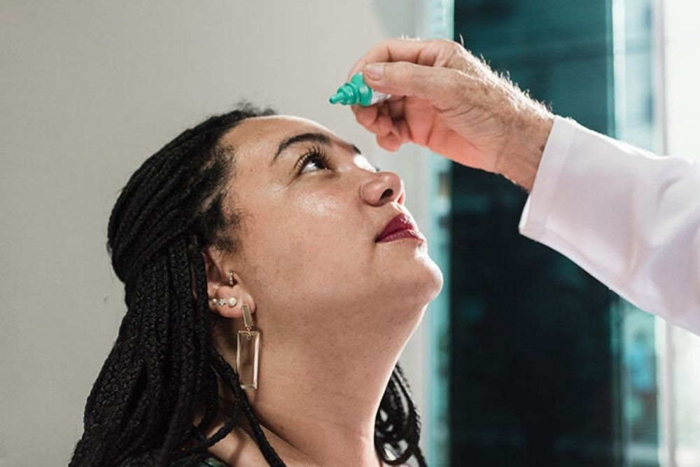 doctor dropping eyedrops on a woman's eye
