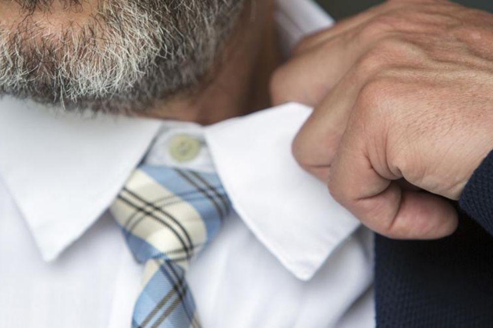 man pulling his collar